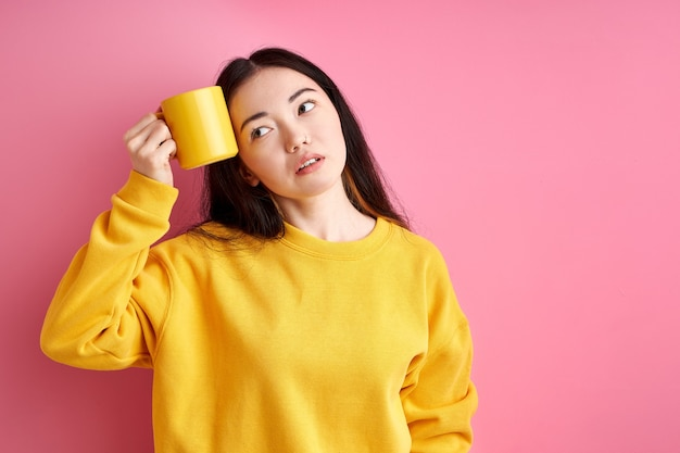 Tired woman try to wake up in the morning, holding cup near head, want to sleep, looking at side, isolated over pink background