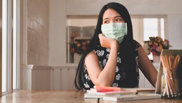 Усталая женщина в медицинской маске смотрит в окно с ноутбуком и канцелярскими принадлежностями на столе. медицинская концепция онлайн-обучение работа из дома