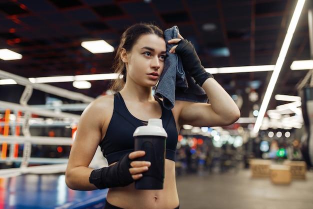 疲れた女性はボクシングのトレーニングの後に彼女の汗を拭き、背景にリング。ジムの女性ボクサー、スポーツクラブの女の子キックボクサー、キックボクシングのトレーニング