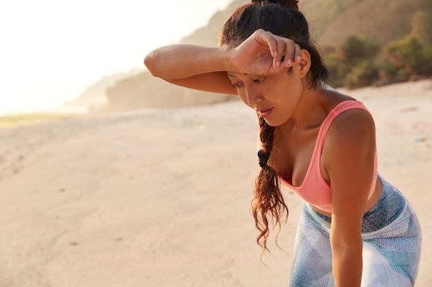 피곤한 여자는 강렬한 체력 훈련 후 이마에서 젖은 물티슈