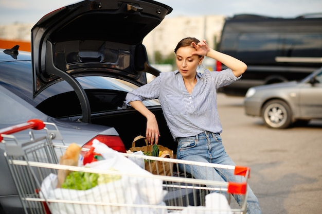 Tired woman with cart puts her purchases in car trunk on supermarket parking. happy customer carrying purchases from the shopping center, vehicles on background