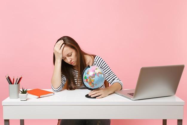Усталая женщина с закрытыми глазами, опираясь на руку, держит глобус, имея проблемы с планированием отпуска, сидя, работая в офисе с ноутбуком
