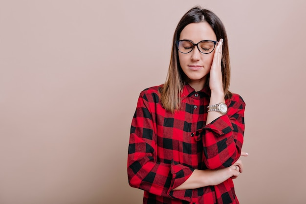 Tired woman with dark hair and closed eyes wears glasses holds hand near the face on isolated wall. the woman with headache poses on beige wall