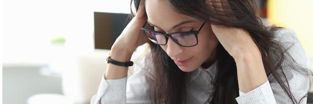 안경 피곤한 여자는 테이블에 앉아 그녀의 손으로 그녀의 머리를 마사지하고 생각합니다.