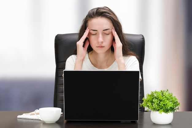 집에서 컴퓨터에서 일하는 두통으로 피곤한 여자