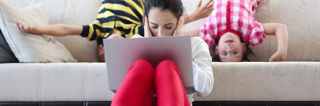 노트북을 들고 피곤한 여성은 소파 아이들이 탐닉하는 뒤에 손바닥 귀를 닫고 바닥에 앉아 있다