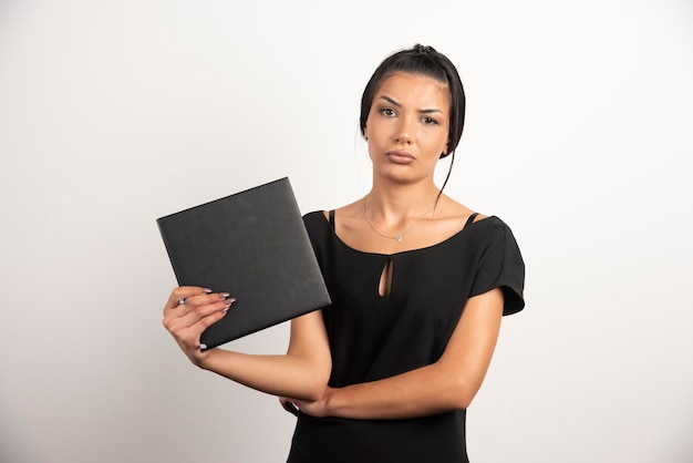Tired woman with notebook looking at camera.