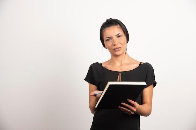ノートを持っている疲れた女性は家に帰りたいです。