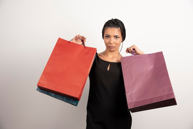Tired woman with shopping bags standing on white wall.