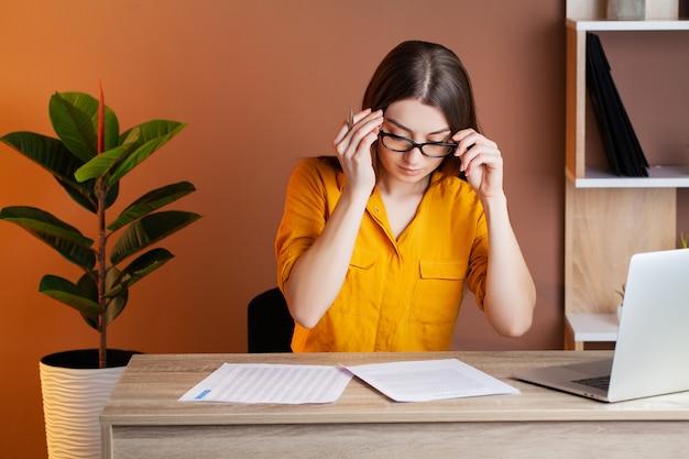 Утомленная женщина работая на компьютере в офисе