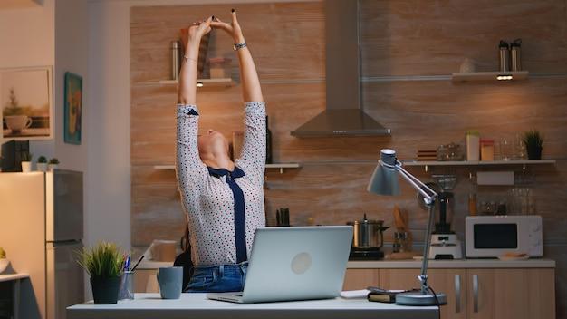 Donna stanca che lavora da casa allungandosi dopo aver digitato sul laptop a tarda notte. impiegato impegnato e concentrato che utilizza la moderna rete di tecnologia wireless che fa gli straordinari per il lavoro che legge la scrittura, la ricerca