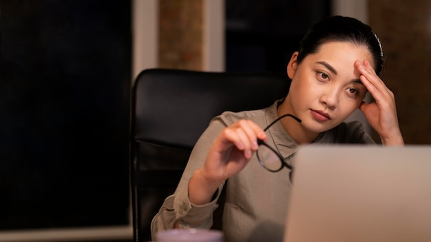 Усталая женщина работает допоздна в офисе