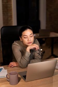 Donna stanca che lavora fino a tardi in ufficio