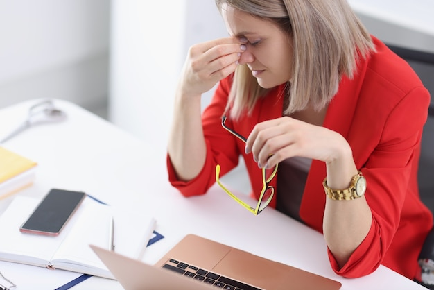 Tired woman at working table in office