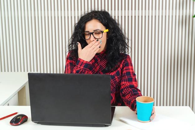 職場であくびをしている疲れた女性。人、仕事、キャリア、過労の概念。オフィスのラップトップコンピューターで働く悲しい忙しいオフィスの女性。働き過ぎの実業家。