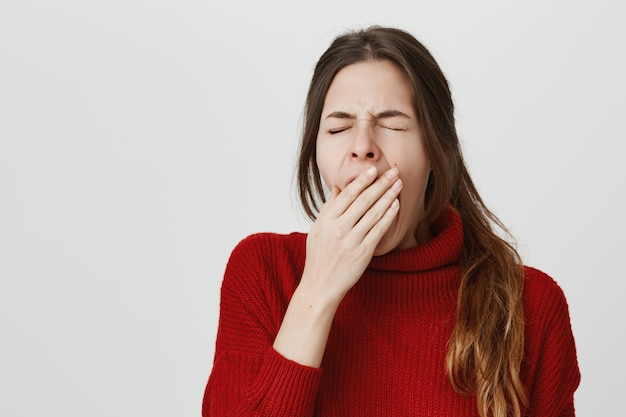 Tired woman yawning, cover opened mouth