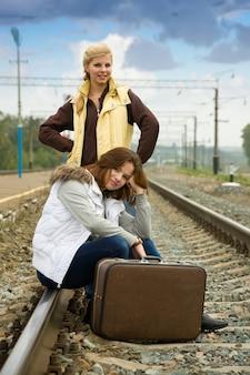 Tired women on rail station