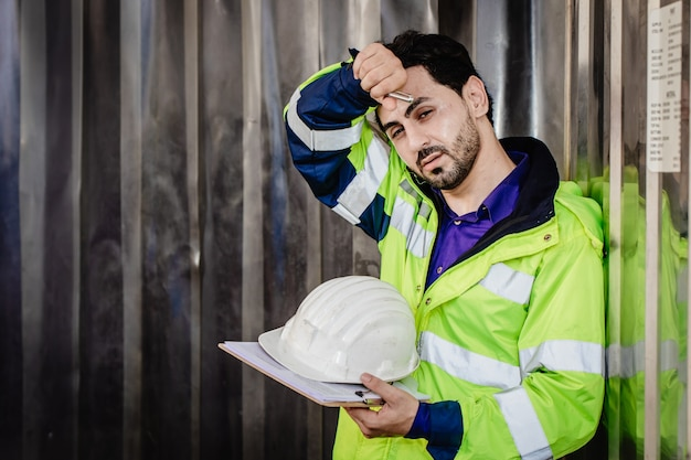 피곤한 노동자, 엔지니어는 중공업 공장에서 일하는 건강에 해로운 더위에 더운 날씨를 겪고 있습니다.