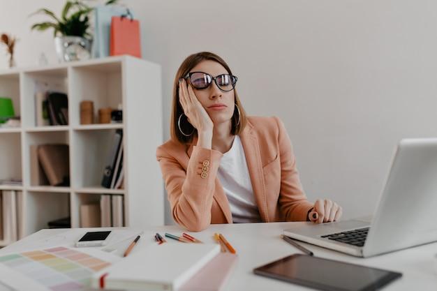 Усталый работник в очках засыпает на рабочем месте. снимок дамы в пиджаке в белом офисе.