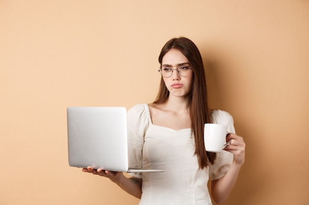 Tired working girl looking at laptop bored, drinking coffee while using computer for work, standing on beige background.
