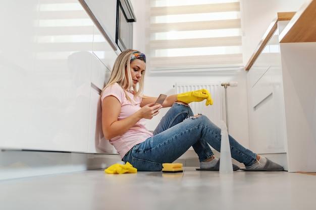 キッチンの床に座って休憩し、ソーシャルメディアサイトにぶら下がっている疲れた価値のある金髪の主婦。
