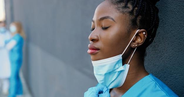피곤 된 젊은 아프리카 계 미국인 여자 의사 의료 마스크를 벗고 휴식 하 고 눈으로 벽에 기대어 동안 뜨거운 음료를 마시 며 폐쇄. 예쁜 여성 간호사 마시는 커피와 휴식 후 열심히