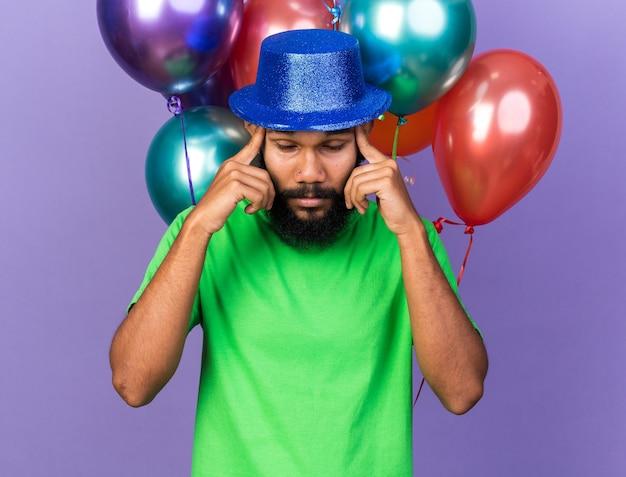 Усталый молодой афро-американский парень в партийной шляпе, стоящий перед воздушными шарами, положив руку на храм, изолированный на синей стене