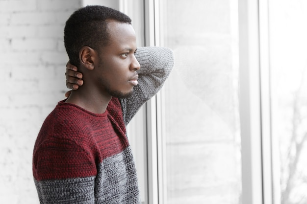Tired young afro-american retoucher wearing casual sweater having small break