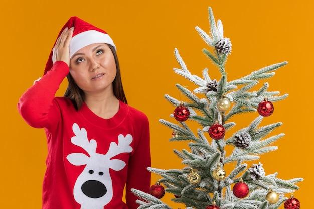 Stanco giovane ragazza asiatica che indossa il cappello di natale con maglione in piedi vicino albero di natale mettendo la mano sulla fronte isolato su sfondo arancione
