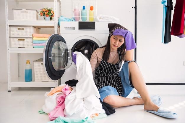 힘든 집안일에 대해 세탁기에서 피곤한 젊은 아시아 주부 두통. 그녀는 수건을 들고 혼자 집안일을 하는 것이 지루함을 느낍니다.