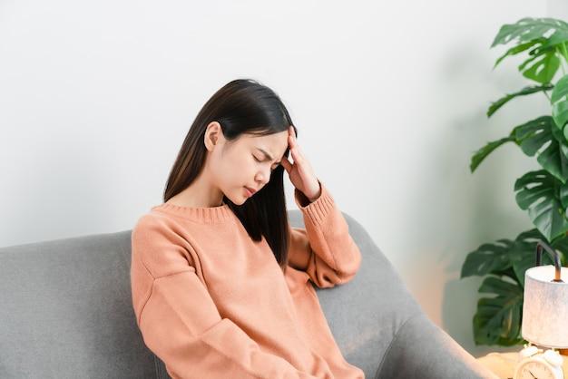 Усталая молодая азиатская женщина сидит и болит голова из-за мигрени.