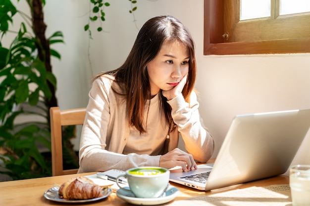Tired young asian woman sitting at a cafe working with a cup of coffee and a croissant