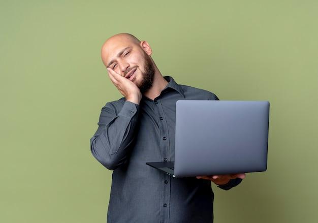 Stanco giovane calvo call center uomo che tiene il computer portatile mettendo la mano sul viso isolato sulla parete verde oliva