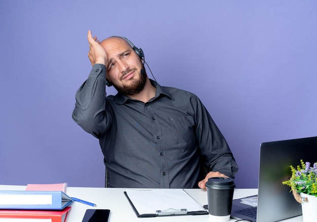 Tired young bald call center man wearing headset sitting at desk with work tools putting hand on head and looking up isolated on purple wall