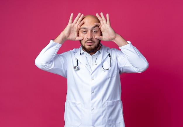 Усталый молодой лысый врач-мужчина в медицинском халате и стетоскопе открывает глаза рукой, изолированной на розовом