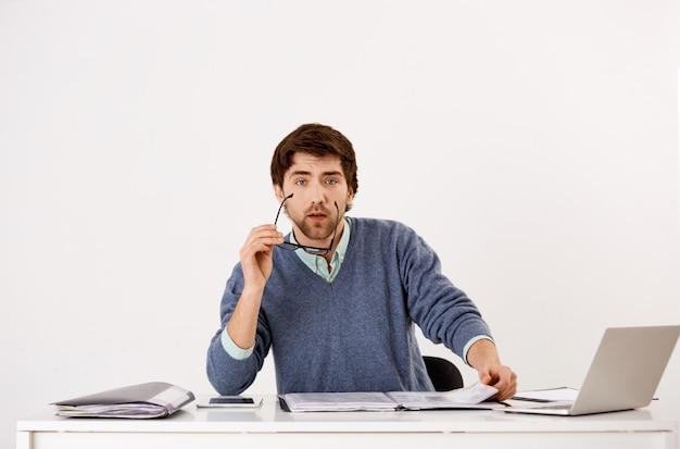 Усталый молодой бородатый парень, офисный работник, прерванный с работы, читающий отчет, снимающий очки, чтобы посмотреть, используя ноутбук