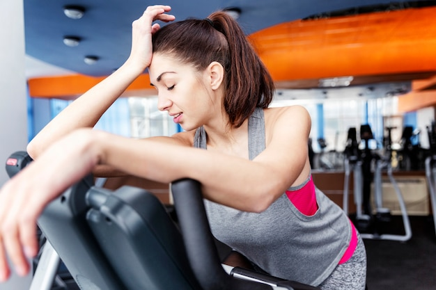Tired young beautiful brunette woman at the gym in the cardio zone.