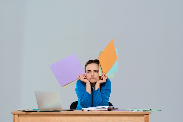 Tired young beautiful businesswoman sitting at workplace, holding colorful folders