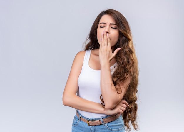 口に手を置き、コピースペースのある孤立した白い壁に目を閉じてあくびをする疲れた若い美しい少女
