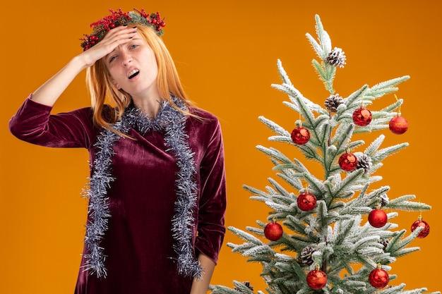 Усталая молодая красивая девушка стоит рядом с елкой в красном платье и венке с гирляндой на шее, положив руку на лоб, изолированный на оранжевом фоне