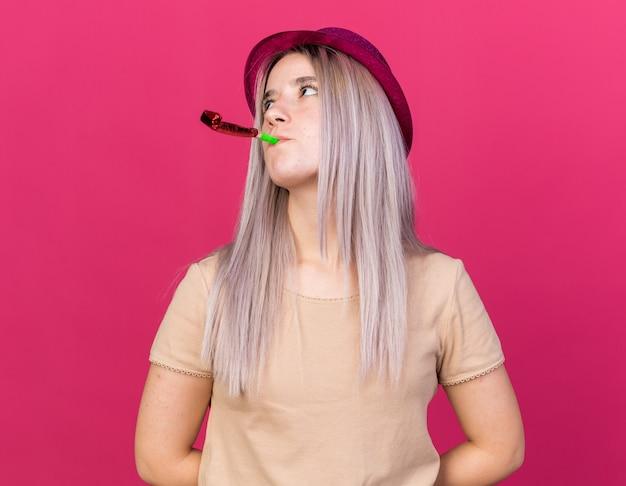 パーティーの笛を吹くパーティーハットを身に着けている疲れた若い美しい少女