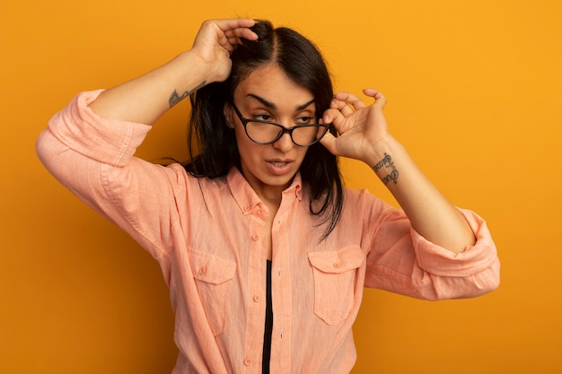 Tired  young beautiful girl wearing pink t-shirt putting hand on head wearing and holding glasses isolated on yellow wall
