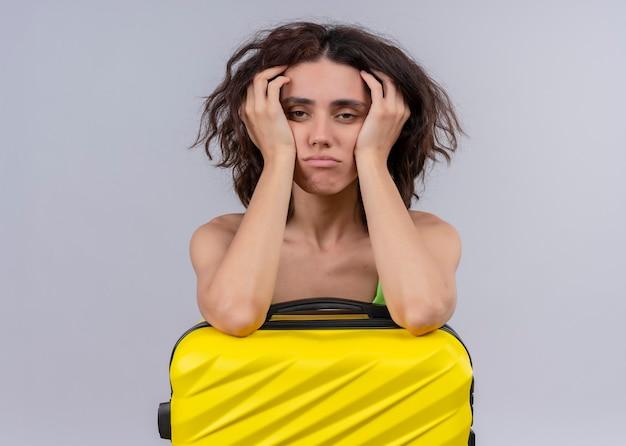 Donna giovane bella viaggiatore stanca che mette le armi sulla valigia e che mette le mani sul fronte sulla parete bianca isolata