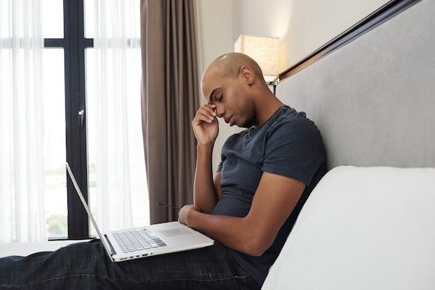 Усталый молодой темнокожий мужчина протирает глаза после целого дня программирования в своей спальне