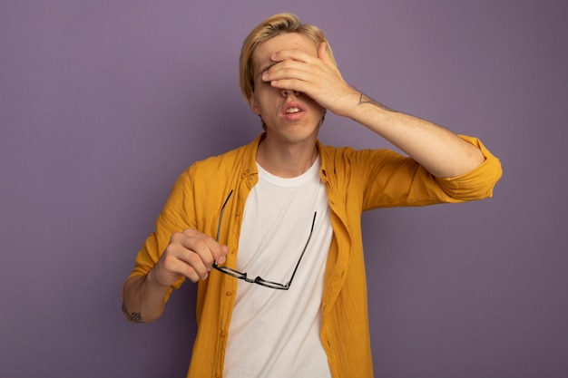 眼鏡を保持し、紫で隔離の手で目を覆った黄色のtシャツを着て疲れた若いブロンドの男