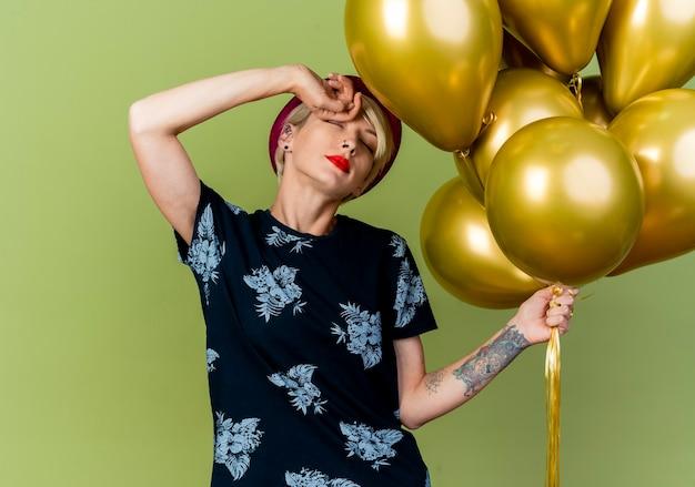Усталая молодая блондинка тусовщица в шляпе партии держит воздушные шары, касаясь лба с закрытыми глазами, изолированными на оливково-зеленом фоне с копией пространства