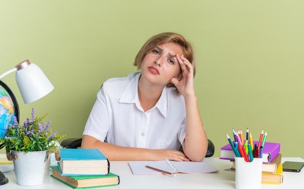 Stanco giovane studentessa bionda seduta alla scrivania con gli strumenti della scuola che tiene la mano sulla testa guardando la telecamera isolata sul muro verde oliva