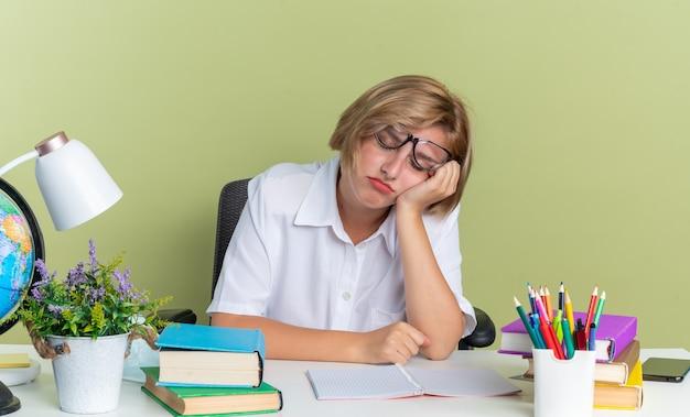 Усталая молодая блондинка студентка в очках сидит за столом со школьными инструментами, держа руку на лице с закрытыми глазами