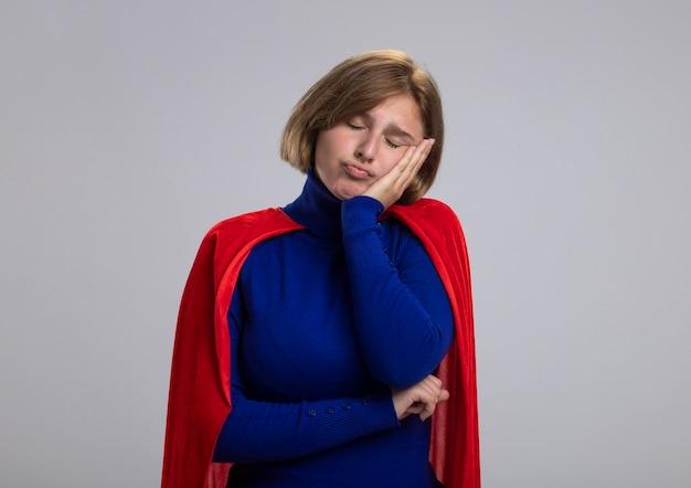 Stanco giovane bionda ragazza del supereroe in mantello rosso mettendo la mano sul viso con gli occhi chiusi isolati su sfondo bianco con copia spazio
