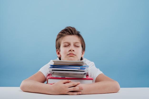 Усталый мальчик и книги усталый мальчик сидит и спит, положив голову на книги, сидя в ...